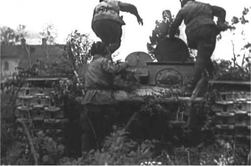Экипаж тягача КВ занимает свои места. 1944 год. Башенный погон закрыт бронелистом, в котором имеется круглый люк — он открыт, и его видно на фото (кадр кинохроники).
