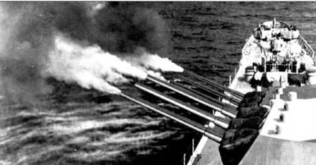 Залп носовых башен главного калибра крейсера «Куинси» по германским позициям в Южной Франции. 15 августа. Крейсер оказывал поддержку силам вторжения, задействованным в операции «Драгун». Клубы дыма от сгоревших пороховых зарядов вырываются из стволов пушек при выстрелах. Специальные экстракторы отсасывают пороховые газы из башен. Обратите внимание на контровую окраску орудийных стволов.