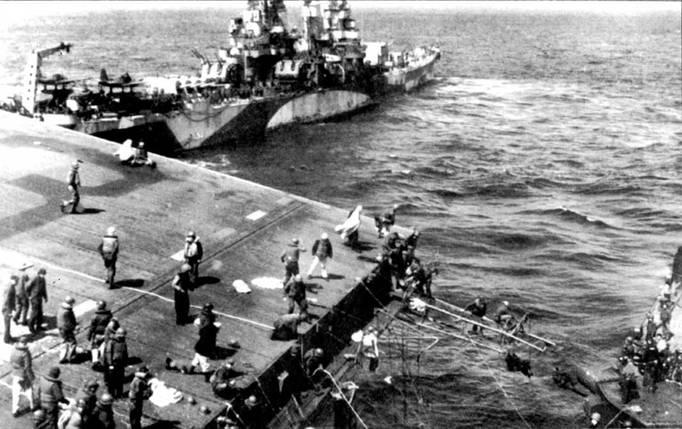 «Питтсбург» кормой к борту поврежден/юго авианосца «Франклин». Справа — людей с авианосца принимает <a href='https://arsenal-info.ru/b/book/2788906538/6' target='_self'>легкий крейсер</a> «Санта Фе». «Франклин» повредили японские бомбардировщики и торпедоносцы 19 мирта 1945г. в момент, когда самолеты «Франклина» наносили удар по Кусю. «Питтсбург» взял поврежденный авианосец на буксир и отвел его в безопасное место.