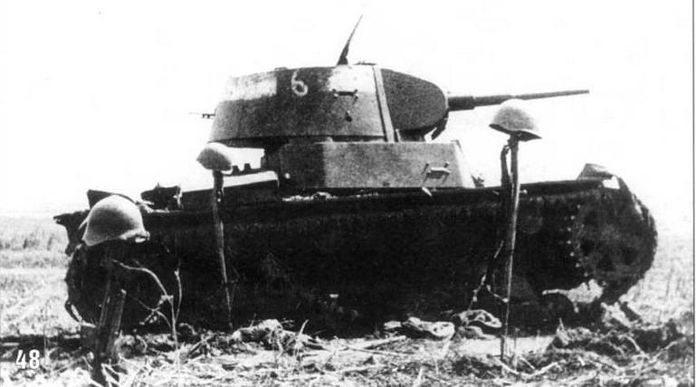Сгоревший танк Т-26 образца 1939 года из состава 18-го механизированного корпуса. Район Умани. Август 1941 г. Каски на винтовках установлены немцами на могилах экипажа танка.