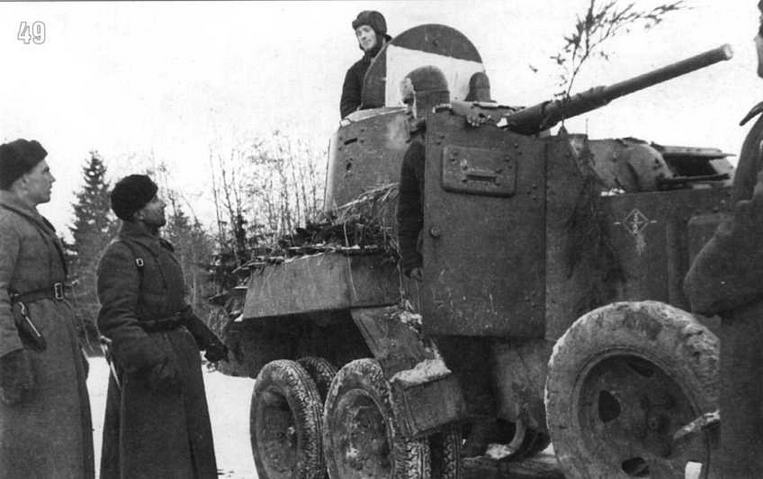 Командир 1-й Гвардейской Танковой бригады (бывшей 4-й Танковой бригады) генерал М.Е.Катуков беседует с командиром бронеавтомобиля БА-10. Верхняя цифра «3» тактического обозначения указывает на номер батальона, нижняя цифра «2» — номер машины. Такая система тактических обозначений просуществовала в соединении генерала Катукова до конца войны. На люке башни белый прямоугольник — знак воздушной идентификации. Западный фронт, Волоколамское направление. Декабрь 1941 г.
