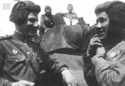 Гвардии старший лейтенант Г.Ш.Аросланов и гв. майор И.И.Кучеренко возле танка Т-34/76. Кроме тактических обозначений на бортах машины (11/33) на поднятых люках виден знак воздушного опознавания — белый треугольник. Воронежский фронт. Июнь 1943 г.