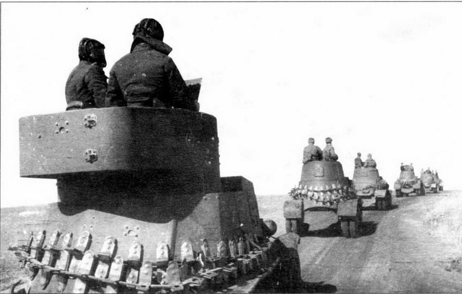 """Подразделение броневиков на марше. На переднем плане — бронеавтомобиль БА-6, на заднем — БА-10. На корпусах боевых машин уложены гусеничные ленты """"Оверолл"""". Западный фронт, 1942 год"""
