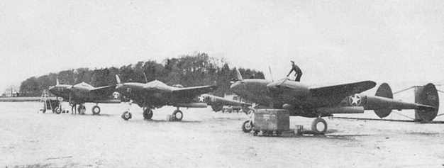 Три Р-38Е из 82-й истребительной авиагруппы. аэродром Лэнгфорд-Лодж, Северная Ирландия. Самолеты осматривают представители 8-й воздушной армии перед перелетом в Северную Африку. Как и на других американских самолетах, действовавшие в Северной Африке, опознавательные знаки «Лайтнингов» обведены желтой каймой.