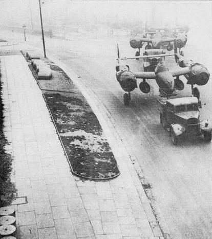 Британский грузовик тащит па буксире шесть «Лайтнингов» P-38F сквозь туман Ливерпуля из доков Гарстоун в аэропорт Спик, где находилось сборочное предприятие фирмы Локхид. Хотя Р-38F мог преодолеть Атлантику по воздуху, большинство самолетов было доставлено в Великобританию транспортными судами.