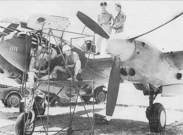 Ремонт P-38F из 96-й истребительной эскадрильи. Пилот самолета лейтенант Лоуренс Либере дискутирует о чем-то с механиком, стоя на центроплане, аэродром Роузуэлл-Хардинг. В одном боевом вылете Либере сбил три итальянских истребителя МС-202 и два повредил. Всего Либере одержал в воздушных боях пять подтвержденных побед.