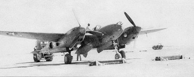 Трактор Cletrac буксирует хвостом вперед P-38F из 82-й истребительной группы 12-й воздушной армии. Самолет тащат на девиационную площадку аэродрома Телегма, Алжир. Под самолетом подвешен один дополнительный топливный бак. Обратите внимание на кругляшок полированного металла на внутренней стороне мотогондолы. Не закрашенный участок поверхности пилот использовал как зеркало для контроля положения носовой опоры шасси.