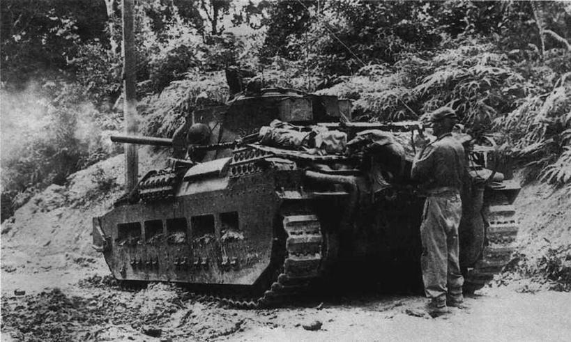 Танк огневой поддержки Matilda CS ведет огонь во время боя на о. Таракан. Пехотный офицер корректирует стрельбу, пользуясь для связи с экипажем телефоном, смонтированным на корме танка. Май 1945 года