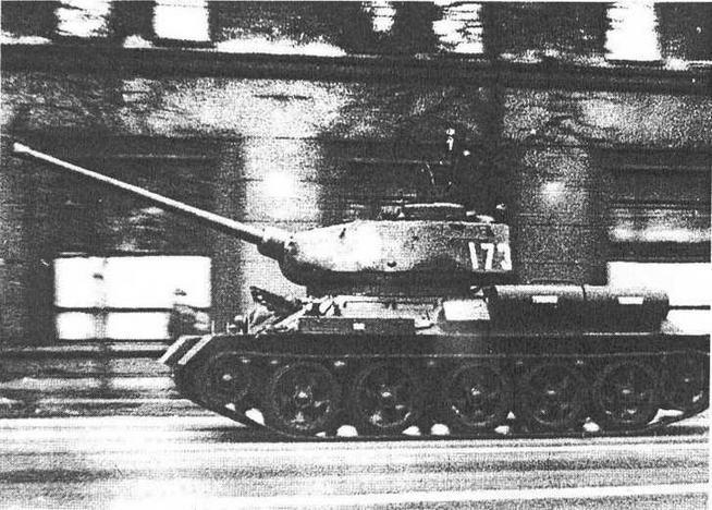 Т-34-85, прошедший заключительный этап модернизации в 60-е годы. Обращают на себя внимание новые опорные катки, форма антенного ввода радиостанции Р-123, а также второй наружный топливный бак и ящик для индивидуального заправочного насоса на левом борту корпуса. Москва, 9 мая 1985 года.