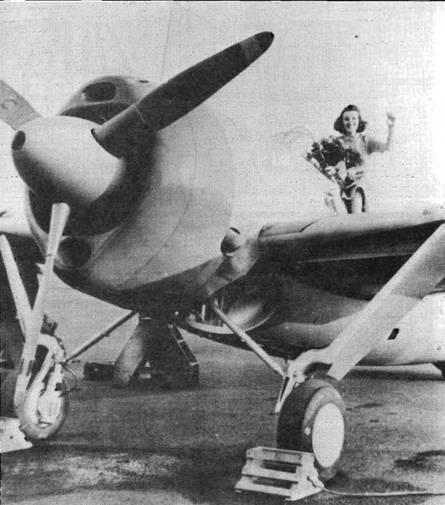 Вероника Тернер, «Мисс Брюстер 1940» позирует у кабины F2A-2 из VF-2 «Flying Chiefs». Эмблема эскадрильи — главный петти-опфицер (Chief Petty Officer)— видна на фюзеляже под фонарем. Колеса шасси оснащены отражателями, прикрывающими оси колес от ударов по тросам аэрофинишера.