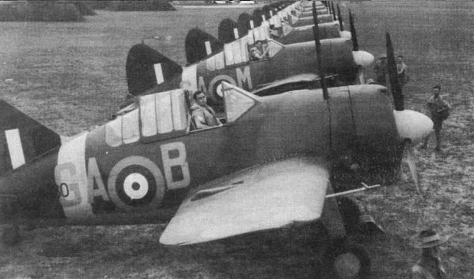 Австралийская 21-я эскадрилья во время инспекции, ноябрь 1941 года. В кабине самолета на переднем плане сидит пилот в спасательном жилете, надетом поверх рубахи с коротким рукавом.