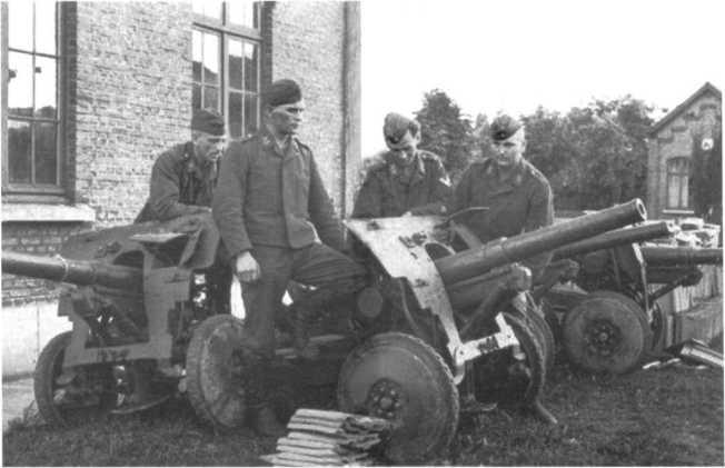 Немецкие солдаты у трофейных бельгийских противотанковых пушек SA.FRS, позже получивших обозначение Pak 185 (Ь). 1940 год (АСКМ).