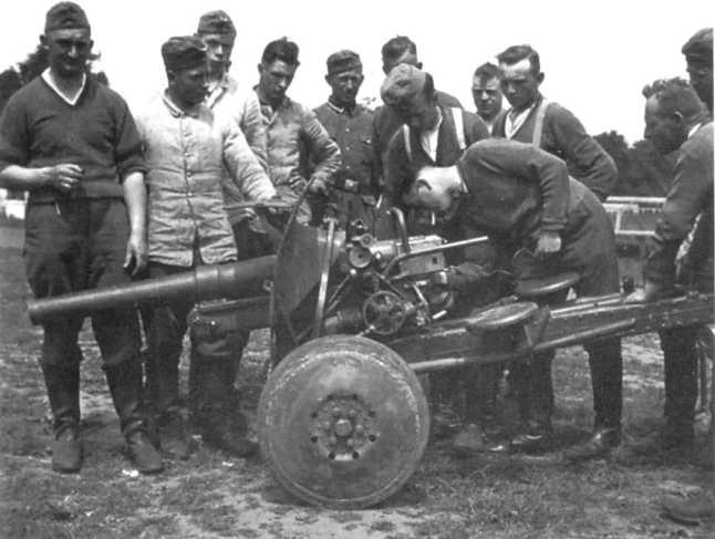 Немецкие солдаты осматривают трофейную бельгийскую противотанковую пушку SA.FRS. 1940 год (АСКМ).
