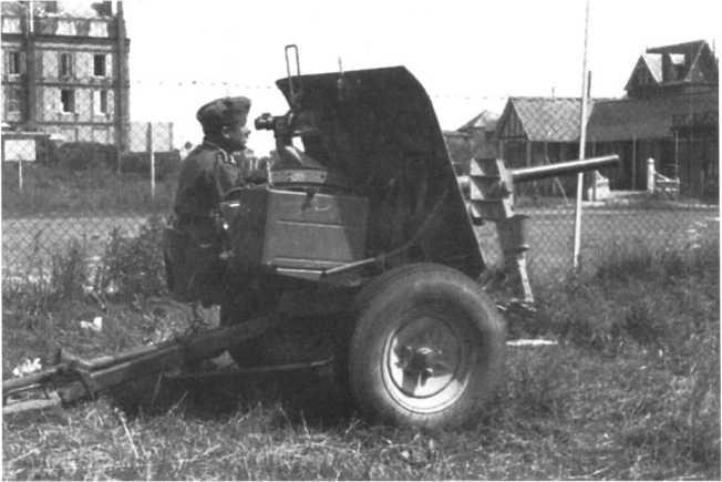 Немецкий артиллерист у английской 40-mm противотанковой пушки Q.F.Мк. VII, получившей обозначение Pak 192 (а). Орудие в походное положении, упоры подняты.