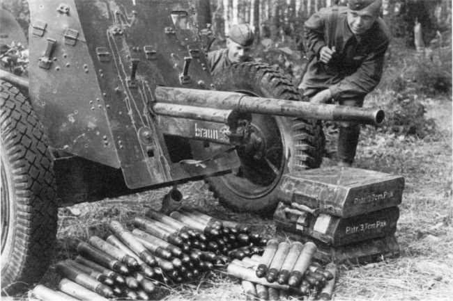 Бойцы Красной Армии осматривают трофеи — 37-мм противотанковую пушку Pak 35/36. Западный фронт, июль 1941 года. Около орудия лежат выстрелы и металлические ящики для их укладки (по 12 штук). На бронировке противооткатного устройства видна надпись «brawn» (РГАКФД).