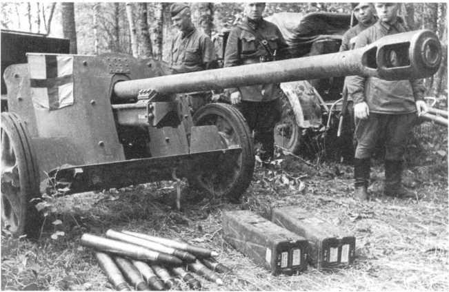 Бойцы и командиры Красной Армии у трофейной 50-мм противотанковой пушки Pak 38. Западный фронт, июль 1941 года. Перед орудием лежат выстрелы и металлические ящики для их укладки (по 4 штуки). Возможно, это одна из первых Pak 38, захваченных советскими войсками (АСКМ).