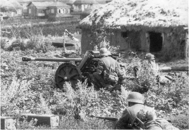 Расчет 50-мм противотанковой пушки Pak 38 поддерживает свою пехоту во время боя за деревню. Июль 1942 года, район Цимлянской. На стволе орудия видны шесть белых колец — число подбитых расчетом советских танков (АСКМ).