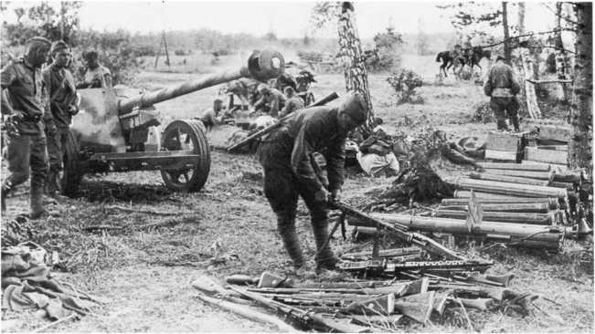 Бойцы Красной Армии осматривают трофеи: 75-мм противотанковую пушку Pak 40 (ту же, что и на предыдущем фото), карабины Mauser 98К, пулеметы MG-34 и MG-42, реактивные противотанковые гранатометы R.Pz. В.54/1. Западный фронт, район Смоленска, лето 1943 года. На заднем плане видны металлические футляры для укладки 75-мм выстрелов (АСКМ).