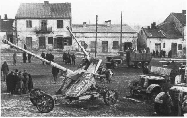 88-мм противотанковые орудия Pak 43 на колесных ходах, брошенные немцами при отступлении в одном из населенных пунктов. 1-й Белорусский фронт, весна 1944 года. Обратите внимание на камуфляж пушек в виде коротких светлых полос, нанесенных поверх базовой окраски. Снимок сделан там же, где и предыдущий (АСКМ).