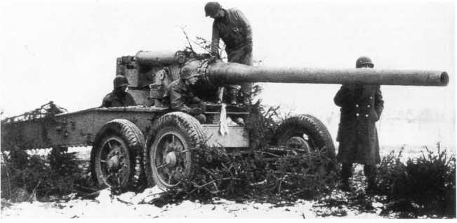 Американские солдаты осматривают 128-мм пушку К 81/1 (на лафете 155-мм французского орудия Canon de 155-mm Grand Puissance Filloux), захваченную в ходе боев в Арденнах. Январь 1945 года (АСКМ).