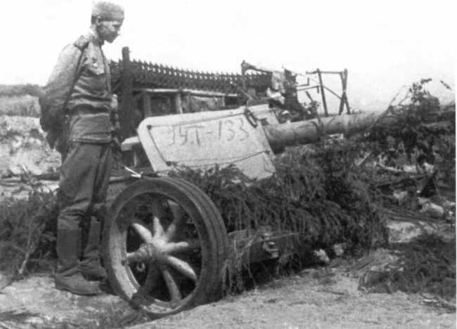 Советский солдат у трофейной немецкой пушки Pak 40. 2-й Прибалтийский фронт, западнее города Опочка, 1944 год (РГАКФД).