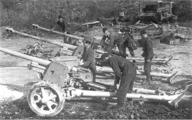 Югославские партизаны изучают 75-мм трофейные немецкие орудия Pak 40, переданные им частями Красной Армии. Сентябрь 1944 года (АСКМ).