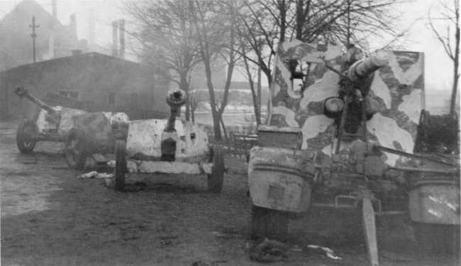 Трофеи советских войск в Восточной Пруссии — справа 88-мм зенитка Flak 36, слева три 75-мм противотанковых орудия Pak 40. Февраль 1945 года (РГАКФД).
