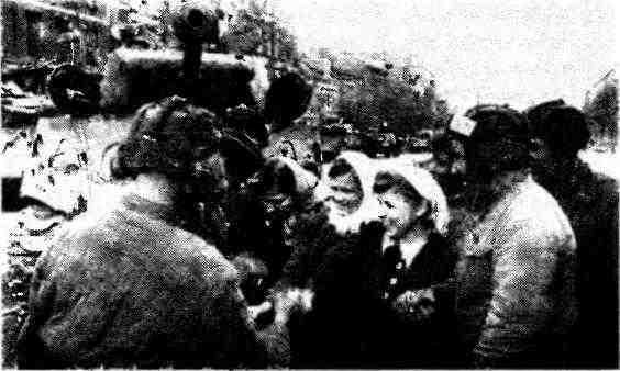 Танкистов приветствуют советские девушки, освобождённые из фашистской неволи. На заднем плане— танк М4А2. Берлин, май 1945 года.
