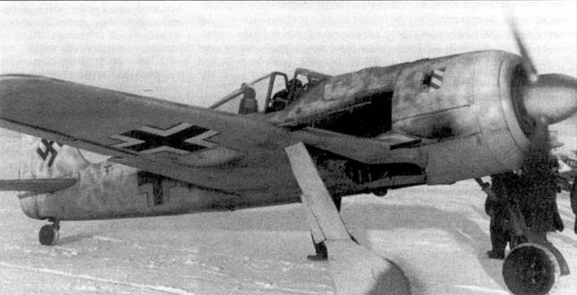 Начало 1943 года. Пилот нового Fw 190A-4, принадлежащего I./JG 54, прогревает двигатель перед взлетом с аэродрома Краспогвардейск. Виден белый зимний камуфляж самолета, особенно плотный в районе желтой полосы быстрой идентификации. Обратите внимание на слой копоти перед правой 20-мм пушкой MG 151, свидетельствующий о активном боевом применении самолета.