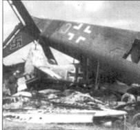 Перевернутый Ju 52 «Mausi» из 2./ Minensuchf'ruppe dev Luftwaffe (3K+CK) лежит поверх истребителя бомбардировщика Fw 190 «желтая С», вероятно принадлежавшего III./SG 3. В последние дни войны эта группа действовала совместно с JG 54.