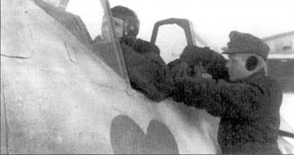 Пока пилот застегивает подбородочный ремень своего летного шлема на меху, механик вытаскивает из-за спины пилота ремни кресла. О стоящих морозах свидетельствуют наушники, которые носит механик. Под фонарем видно «Зеленое сердце» — эмблема JG 54.