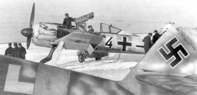 Fw I90A-4 из II./JG 54, стоящий рядом с Bf 109G на аэродроме Сиверская, начало 1943 года. Откинутая крышка открывает доступ к двум пулеметам MG 17 калибра 7,92 мм, втиснутых между двигателем BMW и кокпитом. Несколько недель пребывания на фронте отразились в облезлом зимнем камуфляже и густом слое копоти на бортах.