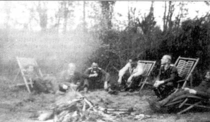 Май 1943 года, аэродром Сиверская. Пилоты из 5./JG 54 коротают время между вылетами у костерки. Среди попавших ни фото летчиков третий слева сидит лейтенант Эмиль Ланг (173 заявленные победы). Поскольку советская авиация постоянно держала под ударом немецкие аэродромы, немецкие пилоты не имели времени на отдых в течение дня. Состояние «готовность 15 минут» означало, что пилоты могли покинуть кабину, но не должны были уд(ияться от самолетов. При этом за каждым таким пилотом закреплялась уже готовая к вылету машина. «Готовность 1час» означала, что точно кто и на каком самолете полетит будет определено в приказе. «Готовность 2 часа» означало, что самолетом занимаются механики, но пилот должен оставаться на аэродроме. Приказ «свободен до такого-то часа» означал, что пилот до указанного часа может отдохнуть. Дежурные звенья сменялись летом каждые 2 часа, а зимой каждые 30 минут. Если дежурное звено поднималось в воздух, следующее по графику звено занимало место на дежурстве.