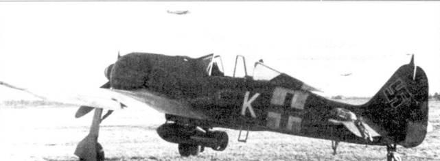 Fw 190А-4 с подвешенной бомбой. Хотя камуфляж его полностью соответствует схеме, принятой в JG 54, появление буквы «К» на борту не совсем понятно. По-видимому, машина принадлежала полу автономной эскадрильи истребителей-бомбардировщиков из состава JG 54. На заднем плане видно взлетающее звено Bf 109.