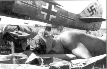 Сиеста. Механик дремлет возле самолета, принадлежащего штабу Gefechtsverband Druschel (SchlG I). Рядом стоит стандартный инструментальный ящик.