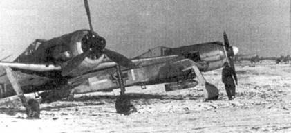 Два Fw 190 с подвешенными бомбами готовятся к вылету по первому снегу. Машина адъютанта группы (передняя, слева) оснащена тропическим фильтром. В зимнее время, когда степная пыль была надежно закрыта слоем снега, необходимость в таком фильтре отпадала. На нижнем снимке панорама аэродрома.