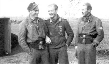 После успешного возвращения из очередного боевого вылета над Румынией, Бухнер шутит с двумя пилотами своего звена (середина 1944 года). Обратите внимание на разнобой в униформе пилотов.