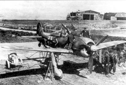 18 июля 1944 года, Дерпт, Эстония. Регулировка вооружения на Fw 190А-6 майора Антона Мадера. На борту фюзеляжа стандартное обозначение машины командира полка: шеврон и горизонтальная полоса. Камуфляж этого А-6 обычный для самолетов Luftflotte 1. Верхние стороны крыльев покрыты пятнами зеленого и коричневого цветов.