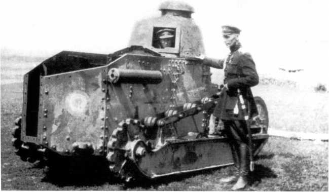 Офицер белой армии у танка «Рено» FT. 1919 год. Машина из состава броневого дивизиона особого назначения при Совете народных комиссаров Украины, о чем свидетельствует эмблема в виде двух концентрических кругов — такая же видна на бронемашине «Пирлесс». Судя по разукомплектованному виду, танк находился на ремонте (ЯМ).