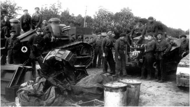 Личный состав 1-го танкового полка польской армии за обслуживанием боевых машин. 1920 год. Слева виден пушечный «Рено» (на нем осталось французское обозначение в виде пикового туза в круге), справа — пулеметный (ЯМ).