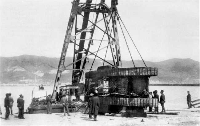 """На этом фото, сделанном красными весной 1920 года, виден плавучий кран (так называемый """"Феодосийский""""), при помощи которого осуществлялась выгрузка прибывающих из Англии танков в Новороссийске. На этом фото краном переворачивают трофейный MK-V, видимо для проведения ремонта (АСКМ)."""