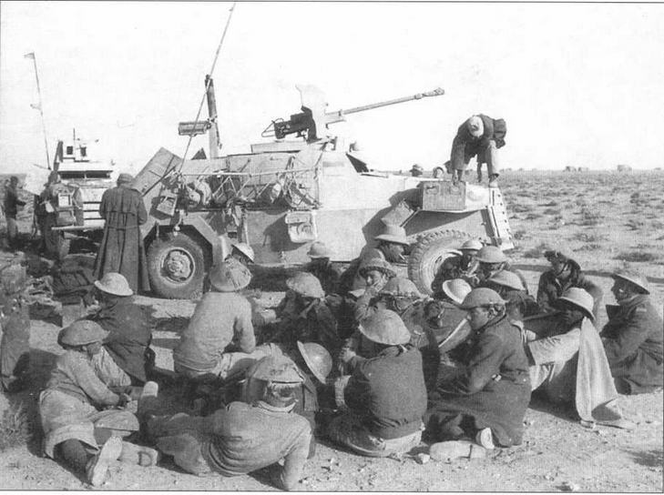 Пленные британские солдаты под охраной трофейных броневиков Marmon-Herrington Mk II (на переднем плане) и Mk III (на заднем). Бронеавтомобиль Mk II вооружен 25-мм французской противотанковой пушкой