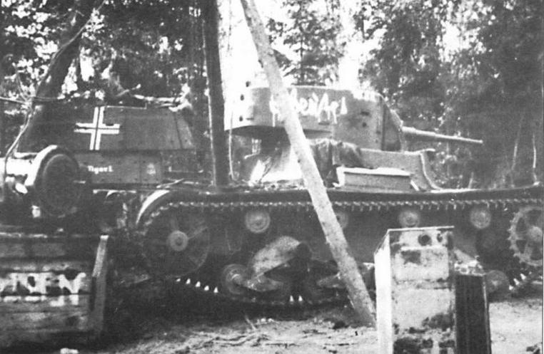 Танки Т-26 в немецкой полевой мастерской. На переднем плане — Т-26 обр.1933 г. с красной звездой и надписью «Захвачен 15-м пехотным полком». На втором плане — Т-26 обр.1939 г. с крестом, названием Tiger II и тактическим значком 3-й танковой дивизии СС «Мертвая голова»