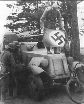 Предотвращая атаку собственной авиации, немецкие солдаты торопятся укрепить флаг со свастикой на захваченном советском бронеавтомобиле БА-10