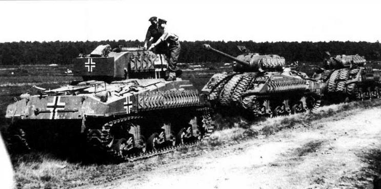 Английские офицеры осматривают группу захваченных у немцев танков «Шерман». В середине группы — танк «Шерман файэфлай». Нормандия, 1944 год