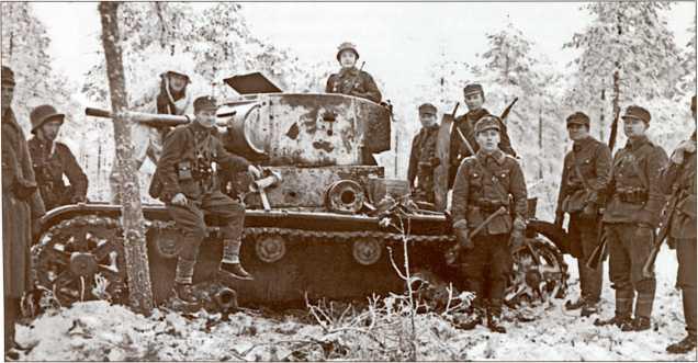 Финский егерь-капитан Лааксо (сидит на танке), командир 3-го батальона 13-го пехотного полка и его подчиненные позируют на подбитом Т-26, Меркки. Хорошо видно пробитие брони на подбашенной коробке танка.
