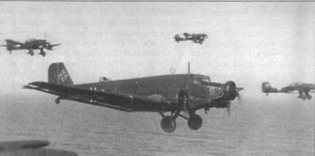 Ju-52/3m g4e в сопровождении трех пикирующих бомбардировщиков Ju-87R держит курс на Крит, май 1941г. Транспортный самолет принадлежит 9-му стаффелю KGzb V-9 (Kampfgeschwader zur besonderen Verwendung, бомбардировочная группа специального назначения). Обратите внимание — окна в грузовой кабине закрыты панелями, причини такой странной доработки не установлена.