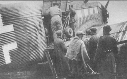 Немецкие солдаты и советские граждане садятся в кабину Ju-52/3m g4e, Восточный фронт, конец 1941г. Желтая полоса вокруг фюзеляжа нанесена сразу за грузовым люком. Стандарты нанесения маркировки далеко не всегда соблюда. и‹сь в полевых условиях.