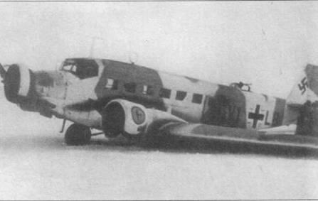 Ju-52/3m g7e (V1+LB) подломил левую опору шасси при посадке на заснеженный аэродром. Восточный фронт. Самолет принадлежит транспортной эскадрилье 7го воздушного корпуса люфтваффе. Верхняя поверхность машины частично окрашена в белый цвет. Эмблема какого подразделения изображена на капоте левого двигателя установить не удалось.