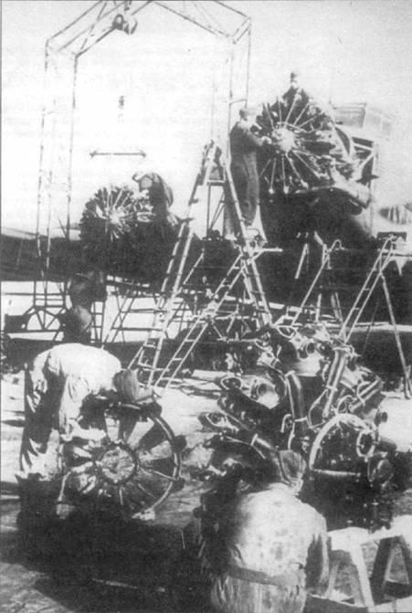 Замена двигателей BMW-132 на самолете Ju-52/3m в полевых условиях. Девятицилиндровый звездообразный двигатель BMW-132 был разработан на основе мотора Пратт энд Уитни «Хорнет». Один из механиков очищает от грязи капот двигателя, второй — возится с самим двигателем.
